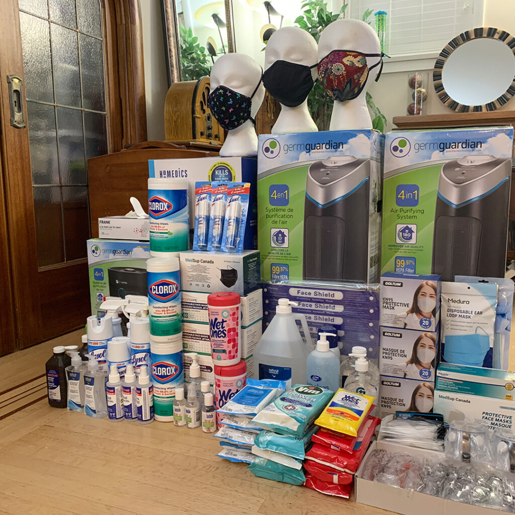 A colourful stack of Covid mitigation items is so large, it resembles a mountain. It includes HEPA air filters, cleaning products, boxes of PPE, and several masks on mannequin heads.