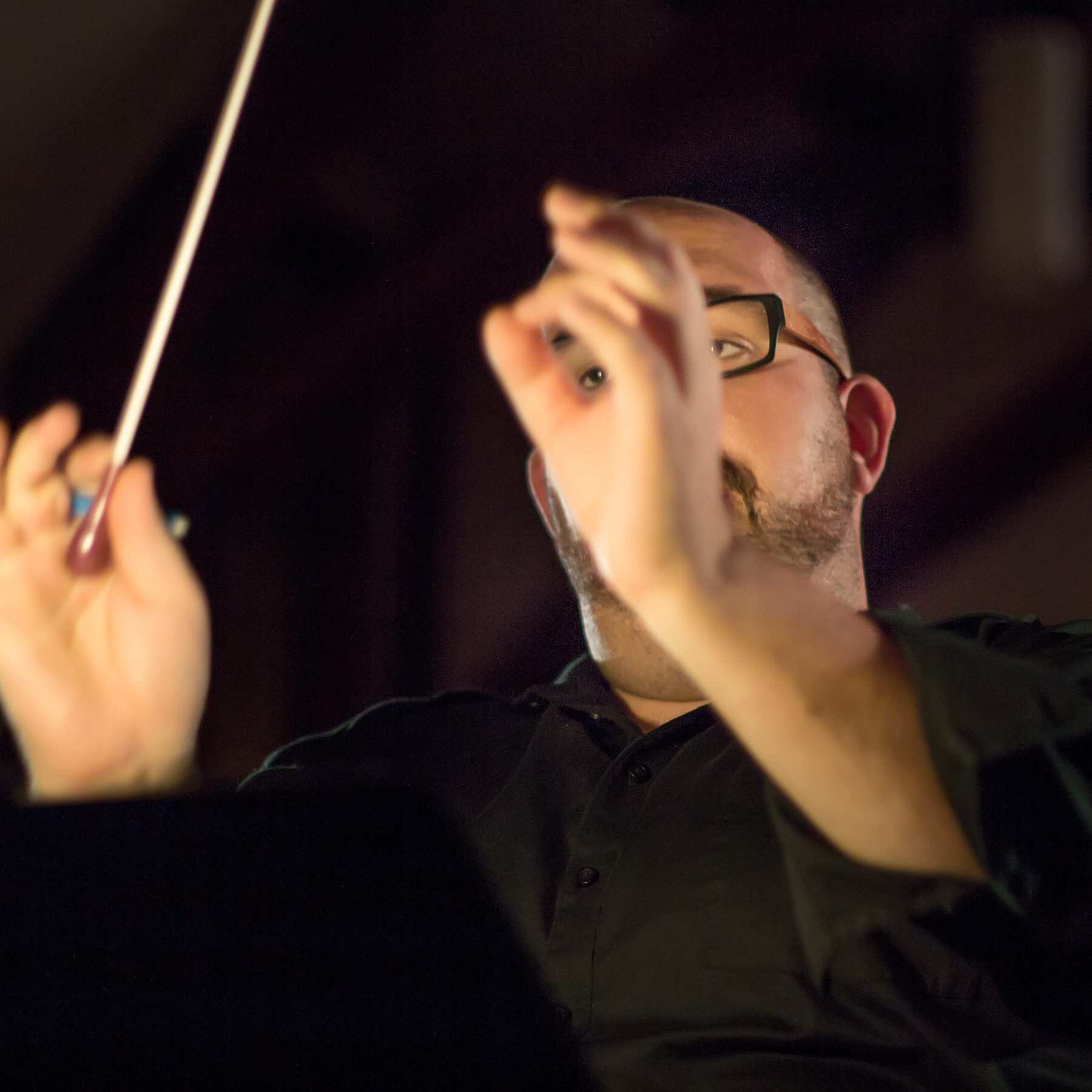 A white man with a beard and glasses wearing a black shirt is conducting in a shadowy theatre. He has his hands raised, with a baton in one hand and the fingers of the other hand cupped in such a way that the viewer can glimpse one of his eyes through his fingers.