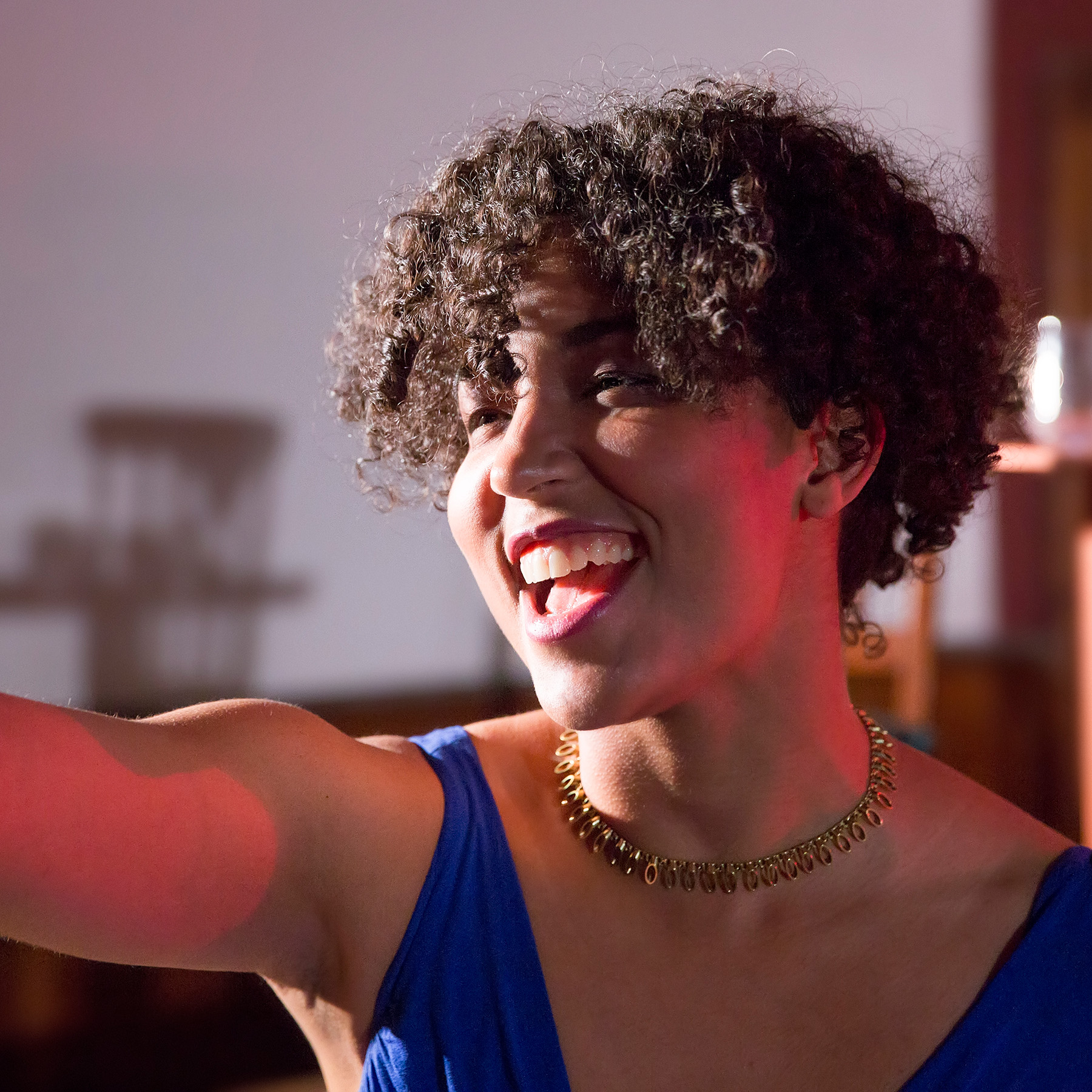 A Black non-binary person with natural hair is onstage, wearing a blue top and gold necklace, bathed in red light. They have one arm outstretched, and a joyous smile on their face.