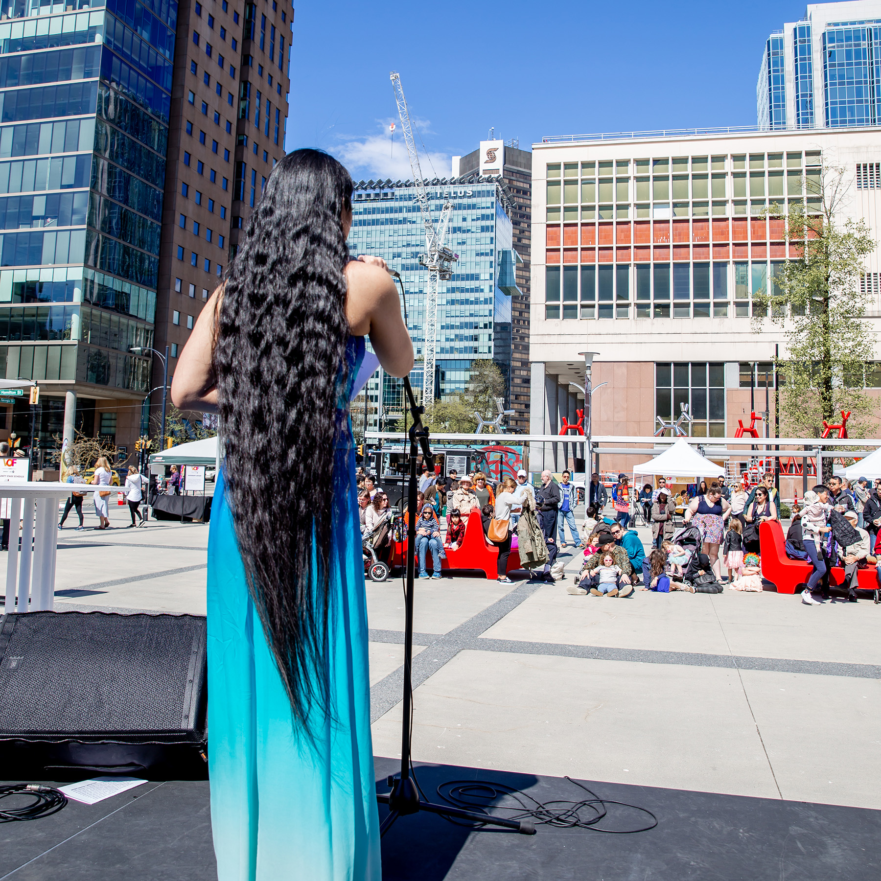 Shown from behind, an Asian Canadian woman with extremely long wavy black hair stands on an outdoor stage, wearing a blue dress, singing into a microphone. In front of her stretches an outdoor plaza, with a crowd enjoying her performance.