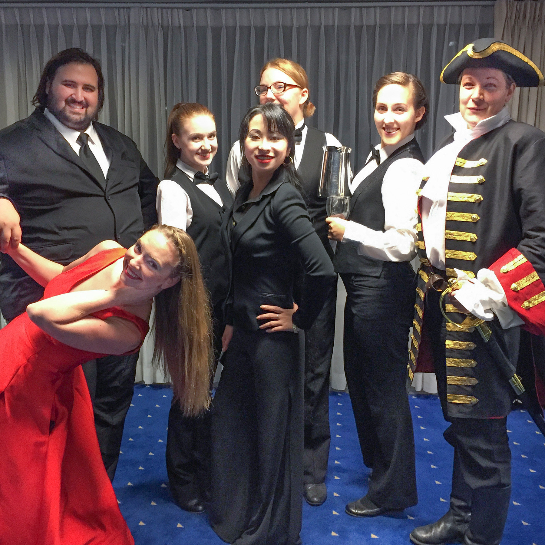 A group of performs with diverse races, body types and gender presentations are dressed as waiters, and holding serving ware. They stand in a hotel room, and smile at the camera. Two of them are dressed differently: one in a red dress, and another in a fancy military uniform.