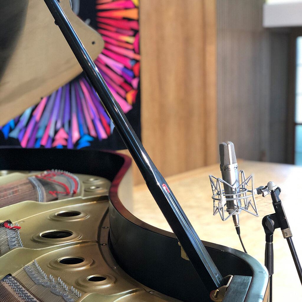 An artistic-ooking image shows the open lid of a grand piano iwth a glimmering gold interior and strings, past which is a gleaming silver studio microphone, an empty stage, and a backdrop decorated with a rainbow starburst pattern.