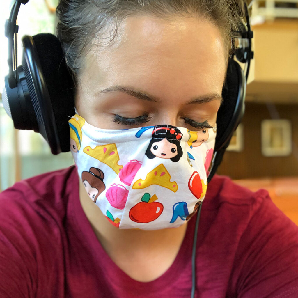 Closeup of Robin Hahn, a femme-presenting human with brown hair, wearing a set of headphones, a red shirt and a colourful mask with a print of cartoon princesses and crowns. Her eyes are closed as she listens intently to the music.