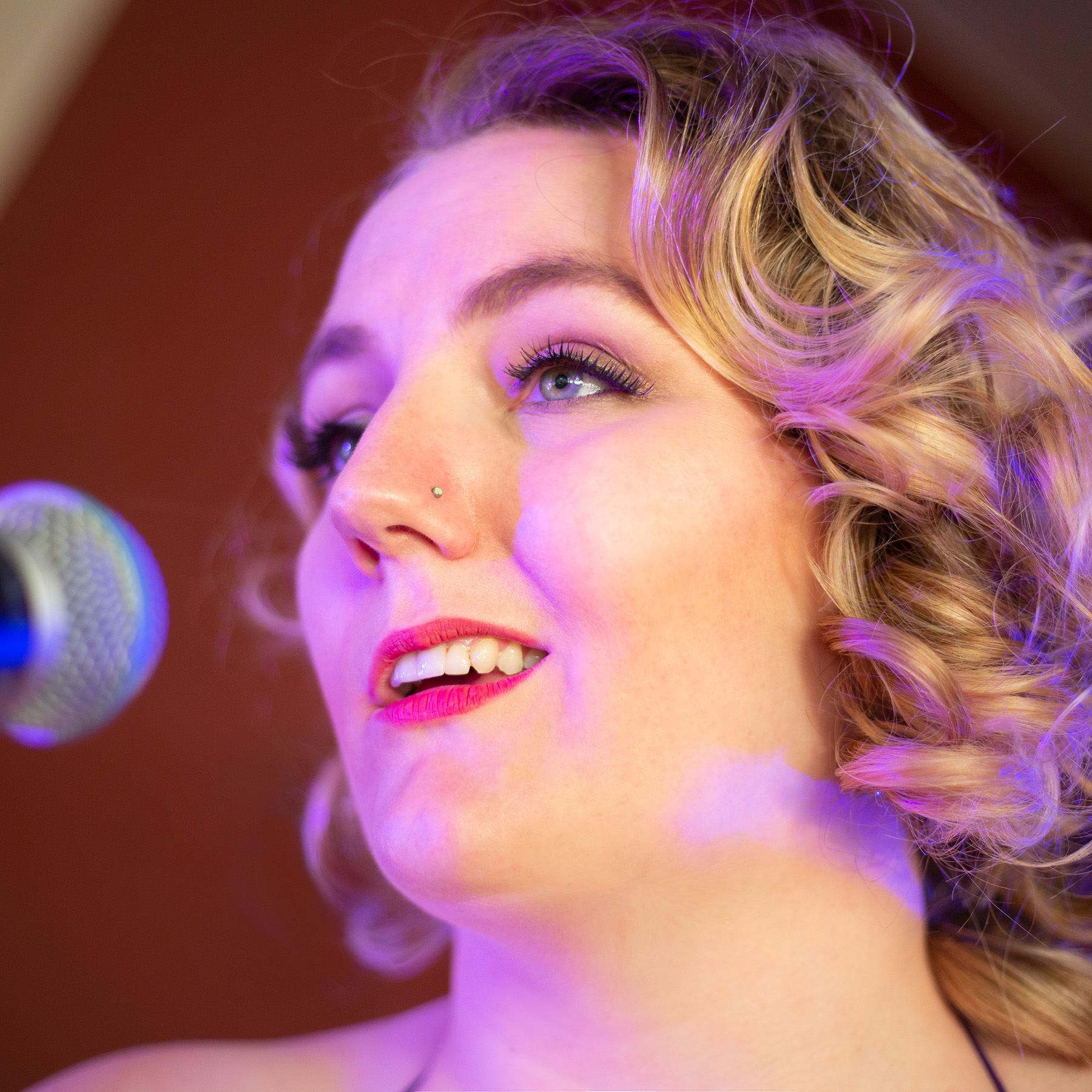 A closeup headshot of a white nonbinary person with blond ringlets, long lashes and a small crystal nose stud, singing into a microphone onstage