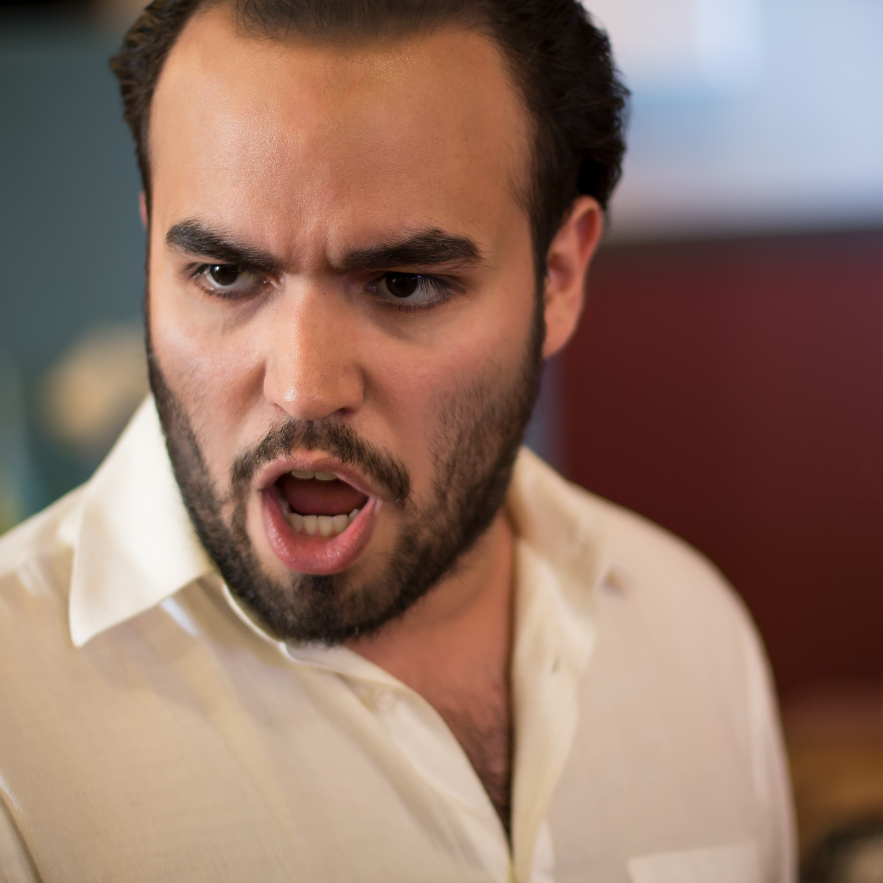 A man of Latino heritage with black hair and a black beard sings onstage with an intense expression on his face.