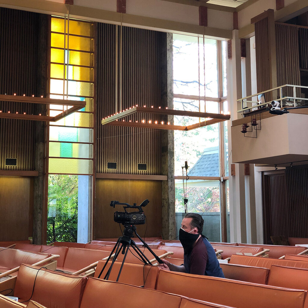In a large mid-century style church full of wood and pale green and gold stained glass, sits the smlal figure of a man wearing a black face mask over a white N-95 face mask and a dark gray shirt. He is operating a large black video camera.